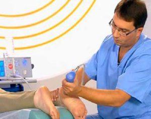 Врач проводит процедуру ударно-волновой терапии
